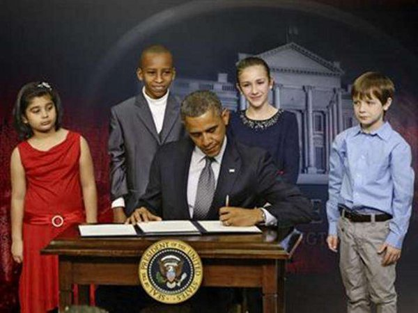 Barack Hussein Obama posing with clueless children