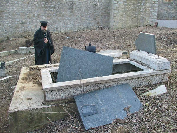 Fr. Nektarios Serfes at a vandalized Serb grave in Kosovo