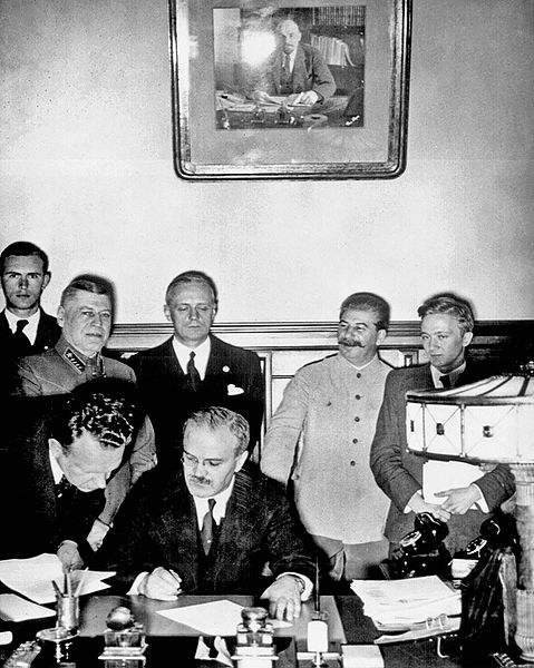 Vyacheslav Molotov signs the Nazi–Soviet non-aggression pact. Behind him are Joachim von Ribbentrop and Josef Stalin.