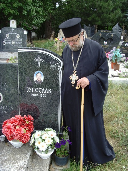 Fr. Nektarios Serfes at a gravesite in Kosovo - click for full view
