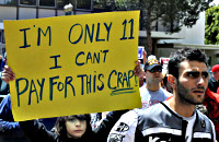 Protest sign: I'm only 11 - I can't pay for this crap!