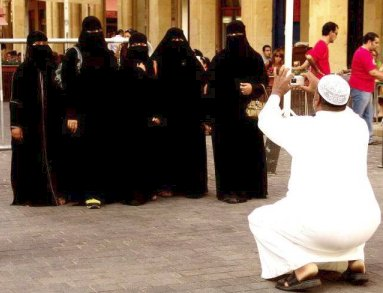 Muslim man photographing a group of fully-veiled women