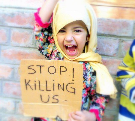 Small girl with scarf around head, with sign 'Stop Killing Us'
